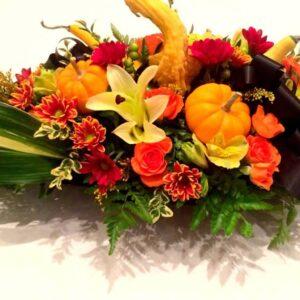 Centre de table naturel avec fleurs d'automne, feuillages et courges